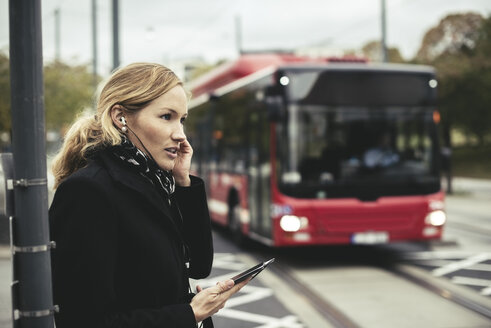 Side view of businesswoman talking on mobile phone with bus in background - MASF02070