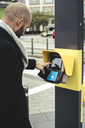 Side view of businessman operating ticket scanner on sidewalk in city - MASF02073