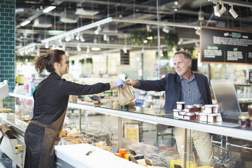 Side view of saleswoman giving package to mature man in organic supermarket - MASF02076