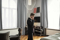 Side view of businessman talking on mobile phone while standing in hotel room - MASF02082