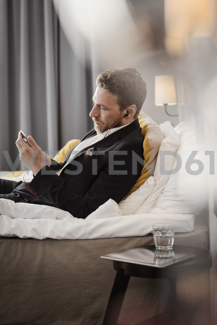 Side view of mature businessman using mobile phone while lying on bed at hotel room - MASF02085