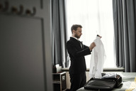 Side view of businessman holding white shirt in coathanger at hotel room - MASF02088