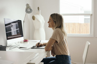 Side view of creative female designer using graphics tablet at home - MASF02100