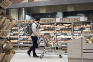 Side view of man walking with cart while looking at breads in supermarket - MASF02106