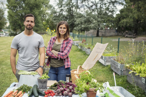 Portrait of mid adult couple standing at table full of freshly harvested garden vegetables - MASF02128