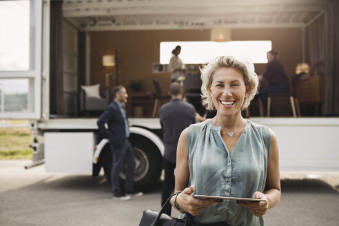 Portrait of happy businesswoman holding digital tablet with colleagues and portable office truck on road in background - MASF02137
