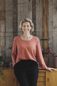 Portrait of smiling businesswoman leaning on sideboard against wood paneling in portable office truck - MASF02140