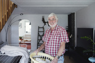 Portrait of smiling senior man holding laundry basket while standing in living room - MASF02155
