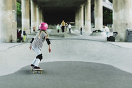 Rear view of girl skateboarding at park - MASF02161