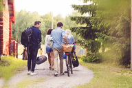 Rear view of friends walking with bicycle and luggage on footpath by trees - MASF02164
