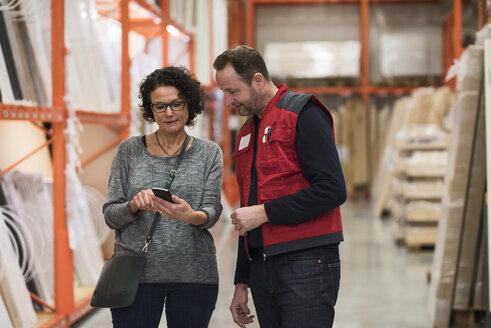 Salesman and female customer using smart phone in hardware store - MASF02173