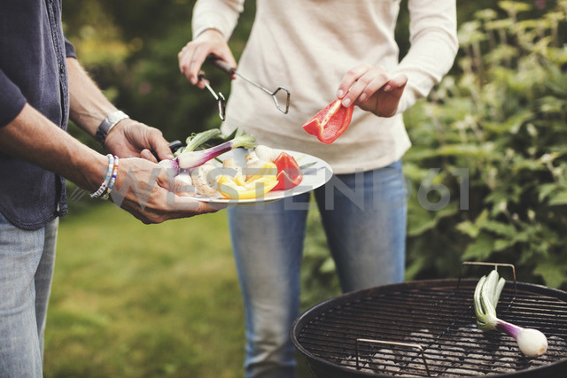 Midsection of father and daughter cooking vegetables on barbecue grill in back yard - MASF02196 - Maskot ./Westend61