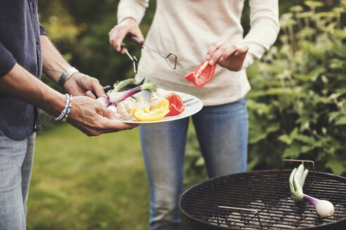 Midsection of father and daughter cooking vegetables on barbecue grill in back yard - MASF02196