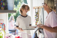 Mother and son holding plates in kitchen at home - MASF02202