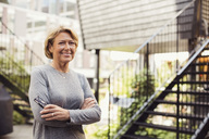 Portrait of confident businesswoman standing arms crossed at office yard - MASF02205
