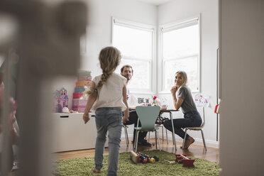 Parents looking at girl walking towards them in playroom - MASF02232