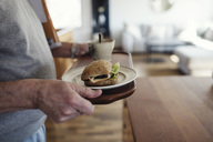 Midsection of senior man holding tray with sandwich and cup at home - MASF02238