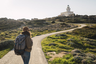 Italy, Sardinia, woman on a hiking trip towards lighthouse - KKAF00929