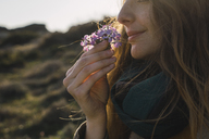 Woman enjoying fragrance of a flower - KKAF00938