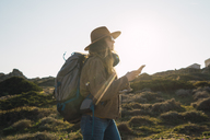 Italy, Sardinia, woman on a hiking trip holding cell phone - KKAF00941