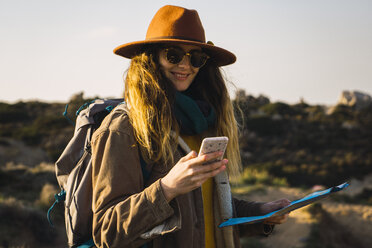 Italy, Sardinia, smiling woman on a hiking trip holding cell phone and map - KKAF00947