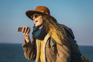 Italy, Sardinia, laughing woman on a hiking trip holding cell phone - KKAF00950