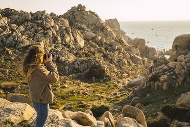 Italy, Sardinia, woman on a hiking trip taking a picture at the coast - KKAF00956