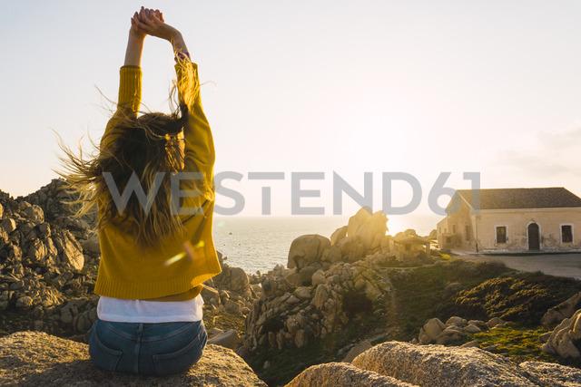 Italy, Sardinia, woman on a hiking trip sitting on rock at the coast raising her arms - KKAF00959 - Kike Arnaiz/Westend61