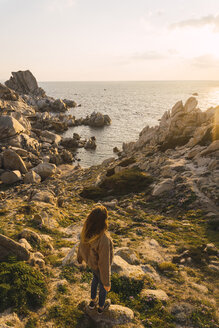 Italy, Sardinia, woman on a hiking trip standing on rock at the coast - KKAF00962