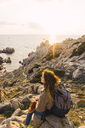 Italy, Sardinia, woman on a hiking trip sitting on rock at the coast - KKAF00965