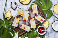 Pina Colada popsicles with candied cherries and pineapple on leaf - RTBF01161