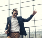 Happy businessman listening to music with headphones - UUF13270