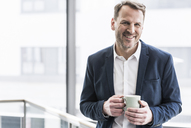 Portrait of smiling businessman having a coffee break - UUF13276