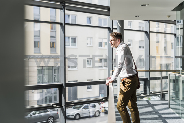 Businessman standing in office building leaning on railing - UUF13282