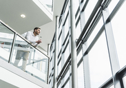 Businessman in office building leaning on railing - UUF13285