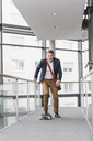 Businessman riding skateboard on office floor - UUF13288