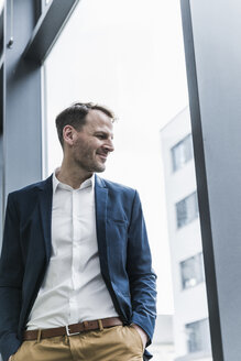 Smiling businessman looking out of window - UUF13294