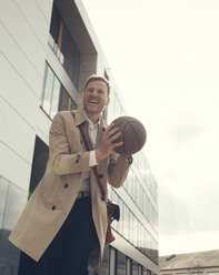 Happy businessman playing basketball outside office building - UUF13297