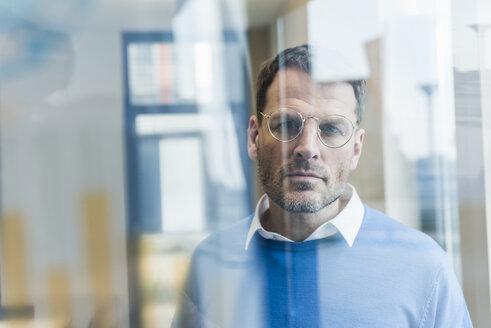 Focused businessman looking at glass pane - UUF13300
