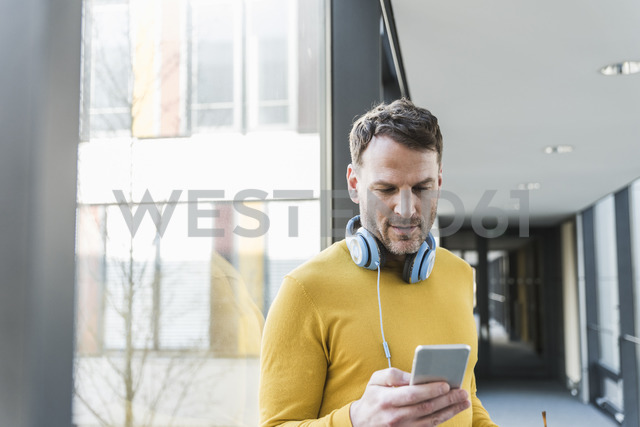 Casual businessman in office using smartphone - UUF13312 - Uwe Umstätter/Westend61