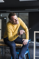 Happy casual businessman sitting on table looking away - UUF13315