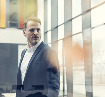 Confident businessman looking out of window - UUF13318