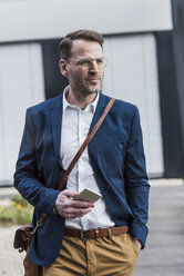 Confident businessman standing outdoors with smartphone - UUF13321