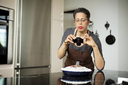 Woman photographing homemade cream tart - CAVF35801
