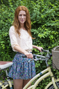 Portrait of woman with bicycle standing at park - CAVF35990