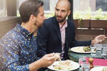 Mid adult businessmen discussing while having lunch at office yard - MASF02243