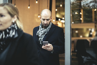 Mid adult businessman using mobile phone while leaving cafe - MASF02264