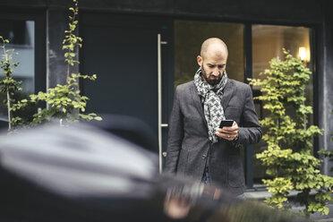 Mid adult businessman using smart phone against building - MASF02267