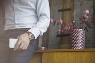 Midsection of businessman holding mobile phone while leaning on sideboard in portable office truck - MASF02282
