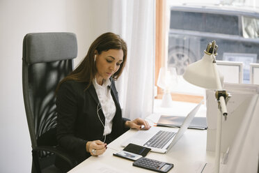 Mature female realtor listening to headphones while looking at laptop in office - MASF02285